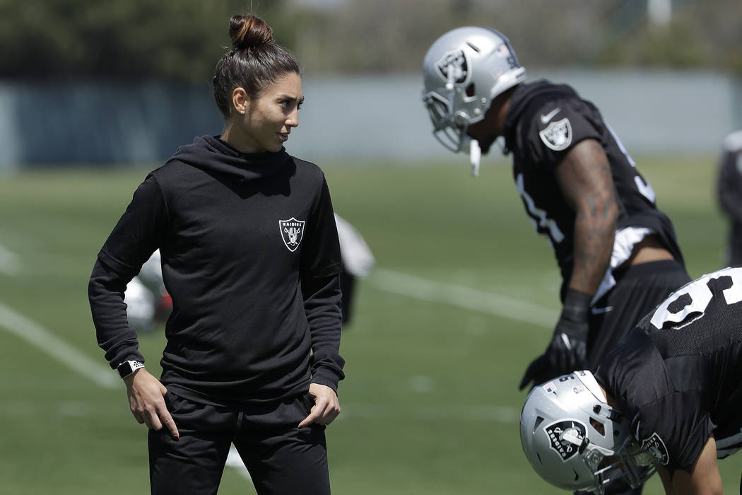 Oakland Raiders strength and conditioning assistant Kelsey Martinez watches as players stretch at the team's football facility in Alameda, Calif., Tuesday, April 24, 2018. (AP Photo/Jeff Chiu)
