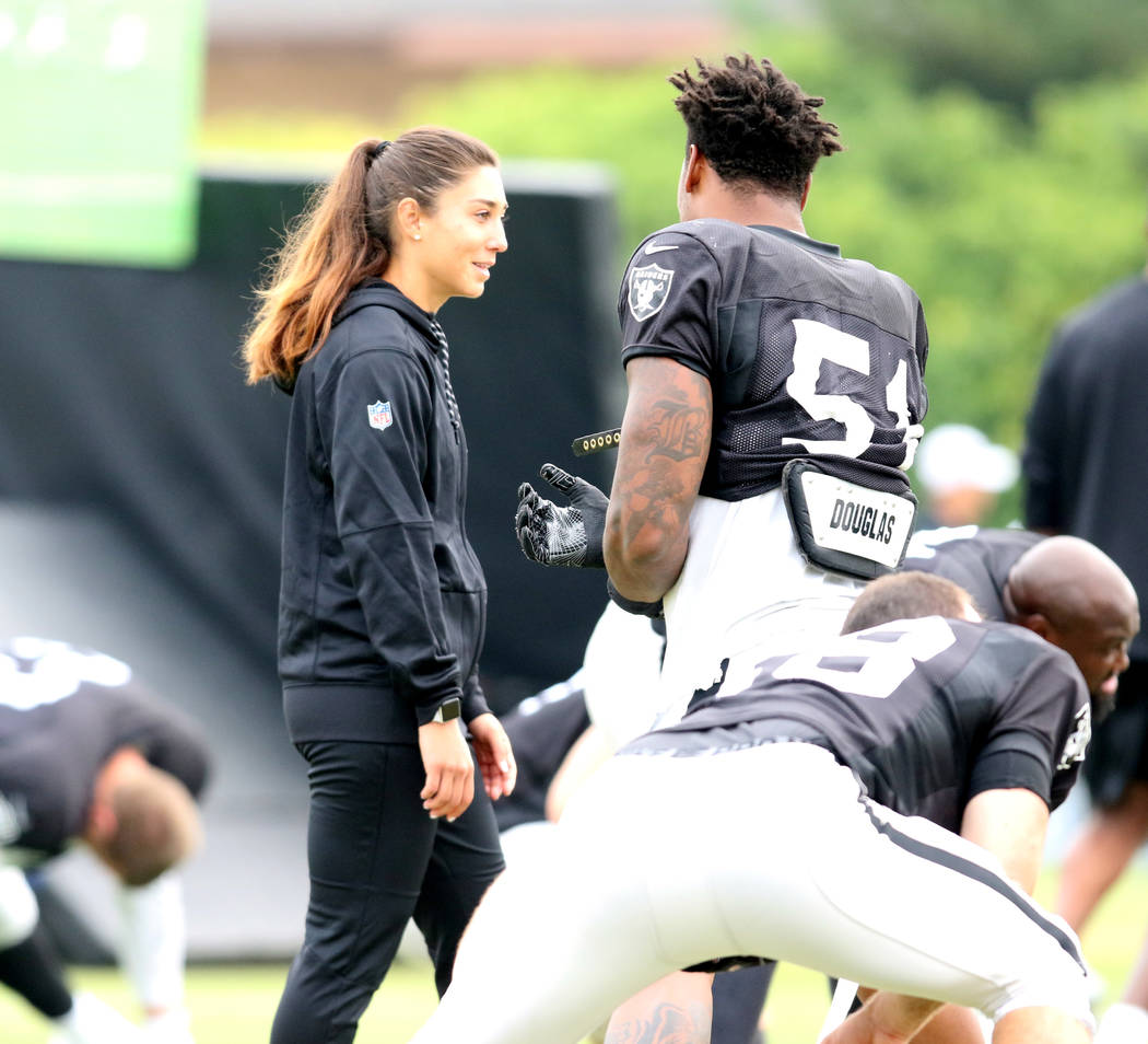 Oakland Raiders strength and conditioning assistant Kelsey Martinez speaks with Oakland Raiders defensive end Bruce Irvin (51) during the warm up session at the team's NFL training camp in Napa, C ...