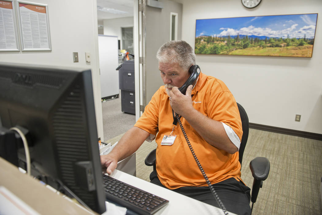 Robert Tierney Jr., right, a patient registration specialist at Mercy Medical Center, who lost his home in the recent fires, works at his job in Redding, Calif., Thursday, Aug. 2, 2018. For the pa ...