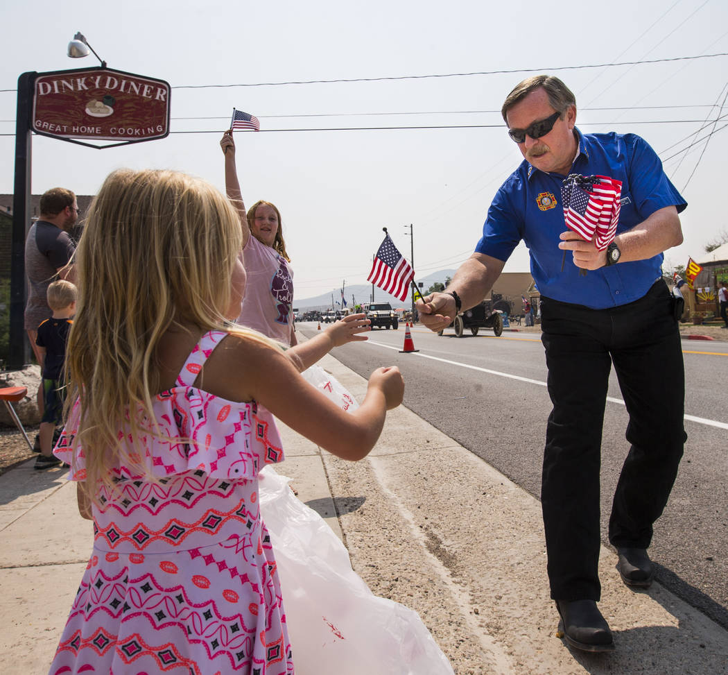 Don Kaminski of Tonopah hands out flags to parade attendees during the Goldfield Days celebration in Goldfield on Saturday, Aug. 4, 2018. Chase Stevens Las Vegas Review-Journal @csstevensphoto
