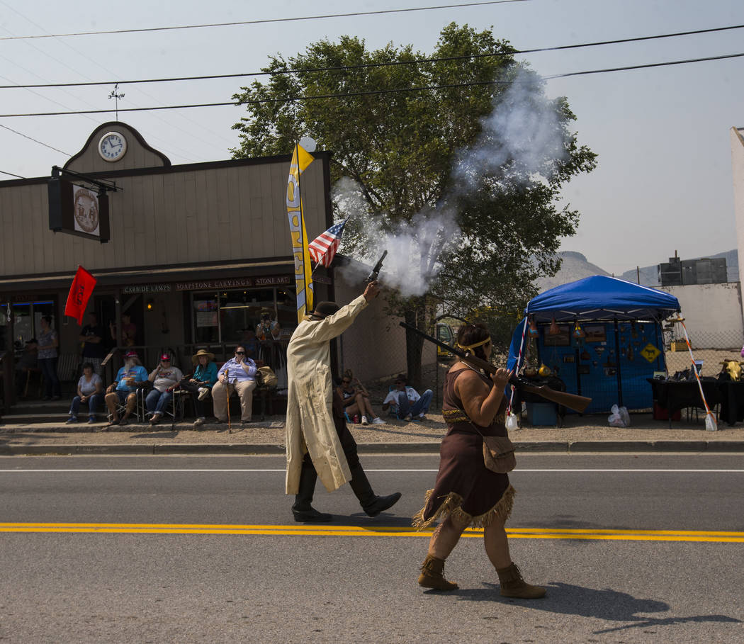 """Don Woolcott, """"The Tonopah Kidd,"""" left, shoots a handgun while participating in the parade during the Goldfield Days celebration in Goldfield on Saturday, Aug. 4, 2018. Chase Stevens Las ..."""