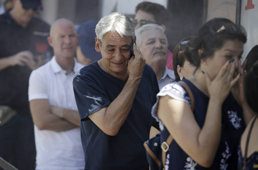 Humberto Berlanga, center, wipes sweat from his face while waiting in the heat. (AP Photo/John Locher)