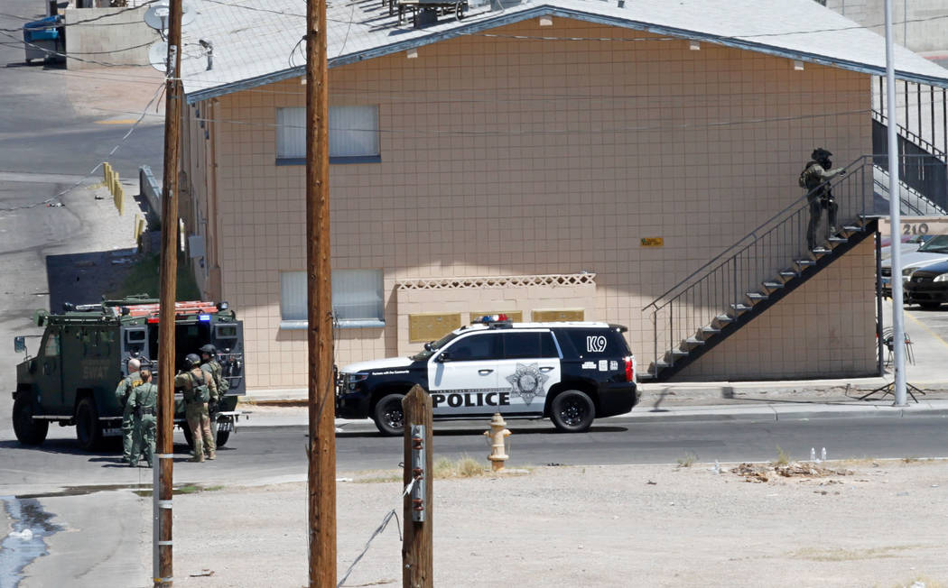 Las Vegas police and a SWAT team are seen around Baltimore Avenue in Las Vegas, Saturday, Aug. 4, 2018. According to Las Vegas police, a man is barricaded inside of a downtown Las Vegas home early ...