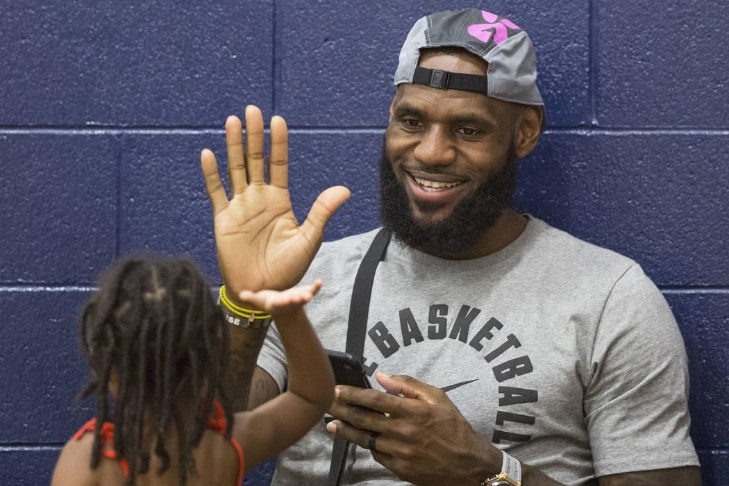 Los Angeles Lakers power forward LeBron James high fives his daughter in Las Vegas. Benjamin Hager Las Vegas Review-Journal @benjaminhphoto