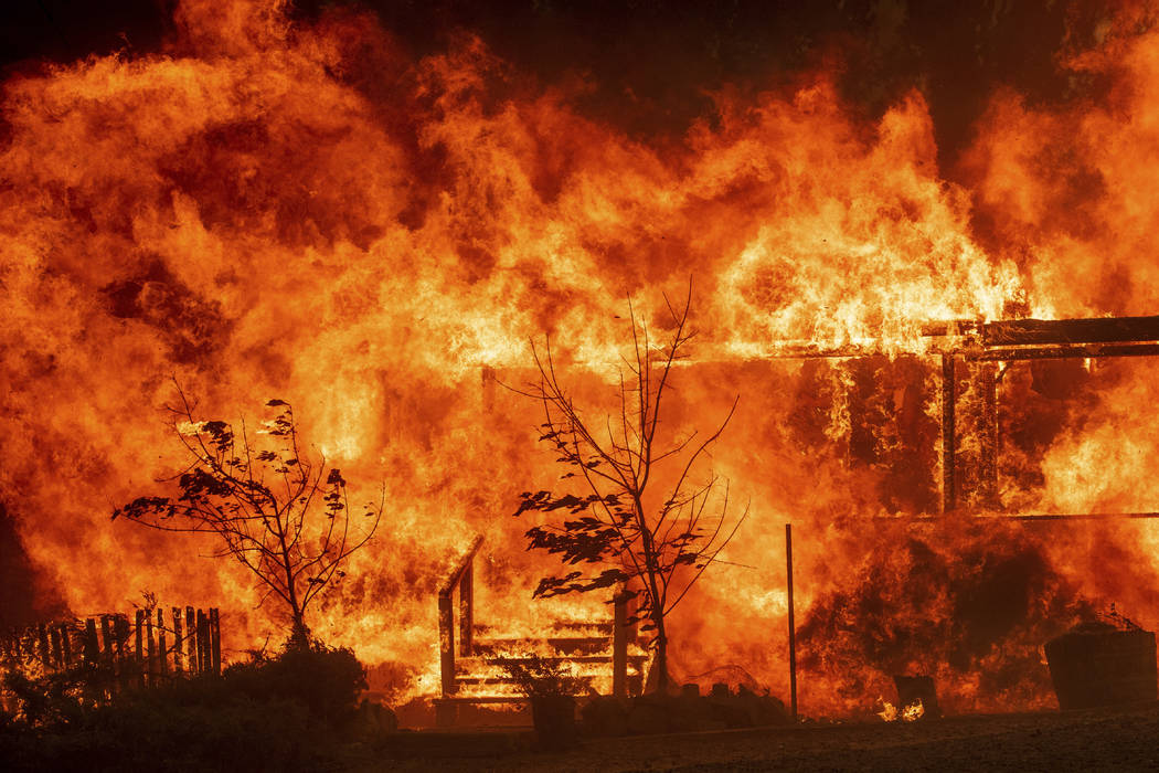 Flames consume a home as the River Fire tears though Lakeport, Calif., on Tuesday, July 31, 2018. (AP Photo/Noah Berger)