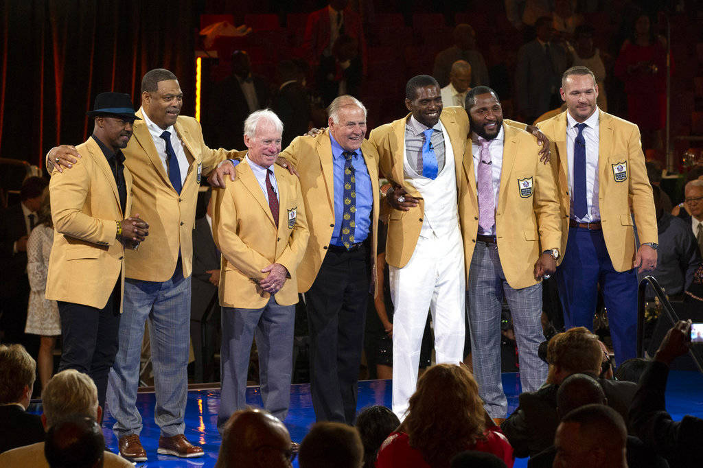 The 2018 Class of the Pro Football Hall of Fame poses during the Pro Football Hall of Fame Enshrinement Festival Enshrinee's Gold Jacket Dinner on Friday, Aug. 3, 2018, in Canton, Ohio. From left ...