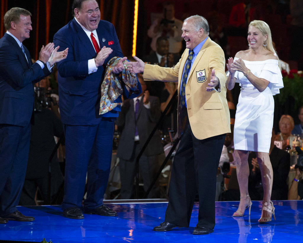 NFL Commissioner Roger Goodell, left, and David Baker, president of the Pro Football Hall of Fame, applaud after Jerry Kramer received his gold jacket from his presenter and daughter, Alicia Krame ...