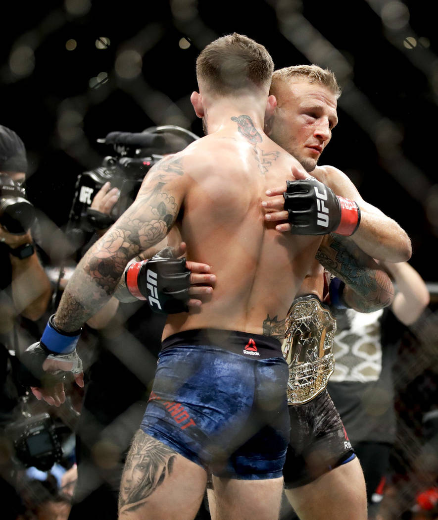 T.J. Dillashaw, right, hugs Cody Garbrandt after Dillashaw's win during their UFC title bantamweight mixed martial arts bout at UFC 227 in Los Angeles, Saturday, Aug. 4, 2018. (AP Photo/Chris Carlson)