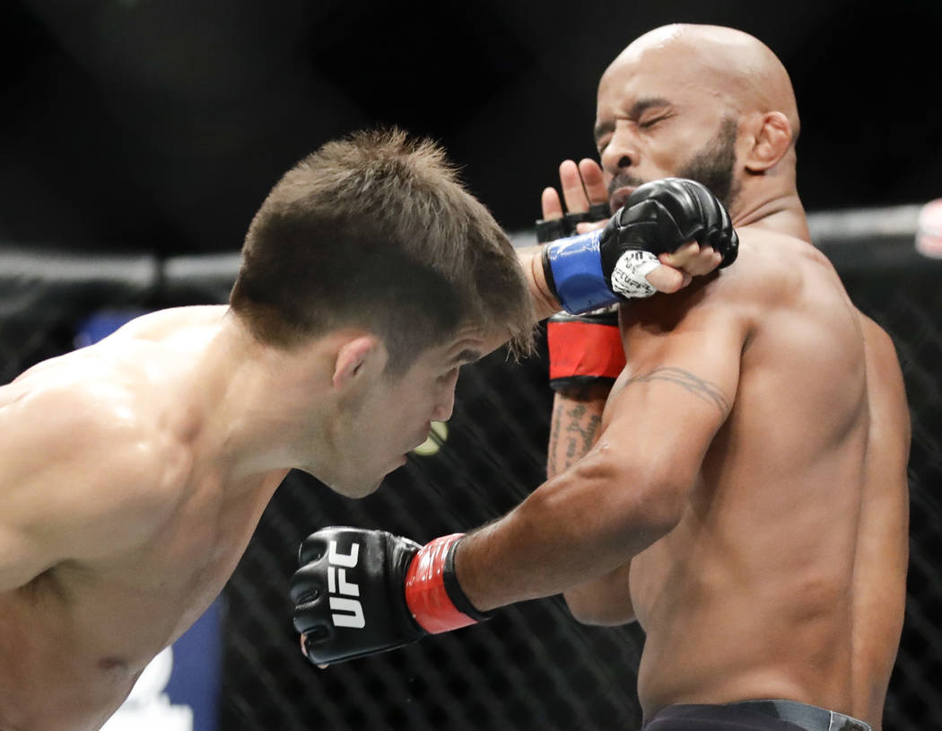 Henry Cejudo, left, hits Demetrious Johnson during their UFC flyweight title mixed martial arts bout at UFC 227 in Los Angeles, Saturday, Aug. 4, 2018. (AP Photo/Chris Carlson)