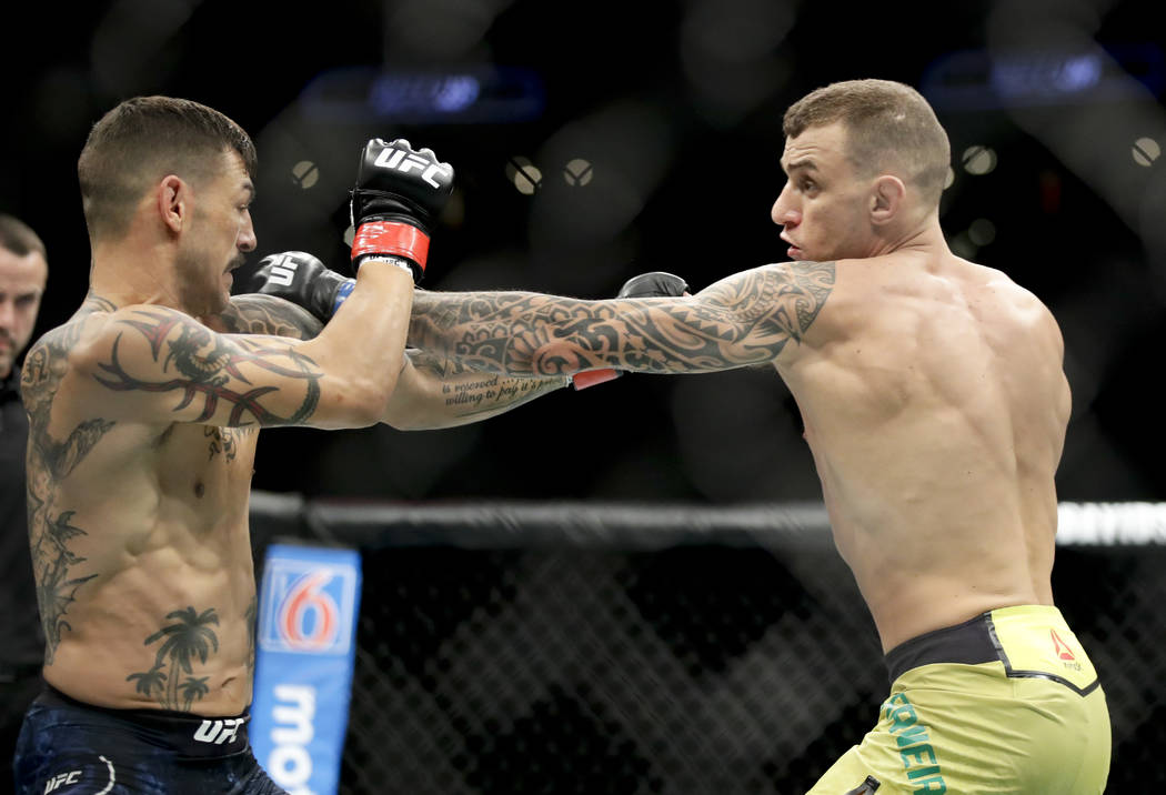 Renato Moicano, right, hits Cub Swanson during their featherweight mixed martial arts bout at UFC 227 in Los Angeles, Saturday, Aug. 4, 2018. (AP Photo/Chris Carlson)