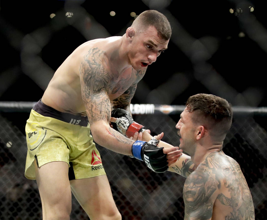 Renato Moicano, left, greets Cub Swanson after the former's win during their featherweight mixed martial arts bout at UFC 227 in Los Angeles, Saturday, Aug. 4, 2018. (AP Photo/Chris Carlson)