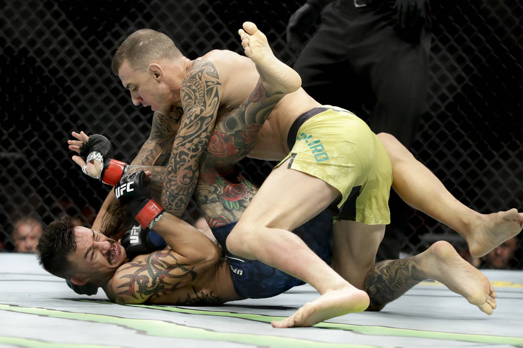 Renato Moicano, top, hits Cub Swanson during their featherweight mixed martial arts bout at UFC 227 in Los Angeles, Saturday, Aug. 4, 2018. (AP Photo/Chris Carlson)