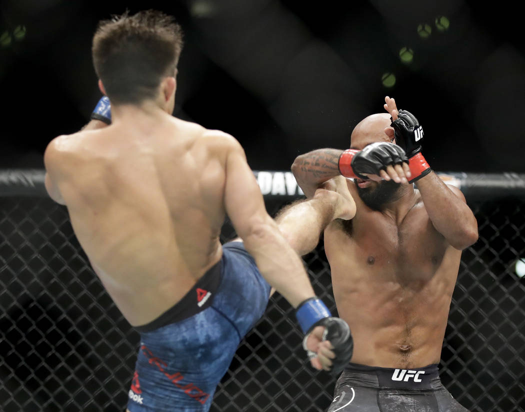 Henry Cejudo, left, kicks Demetrious Johnson during their UFC flyweight title mixed martial arts bout at UFC 227 in Los Angeles, Saturday, Aug. 4, 2018. (AP Photo/Chris Carlson)