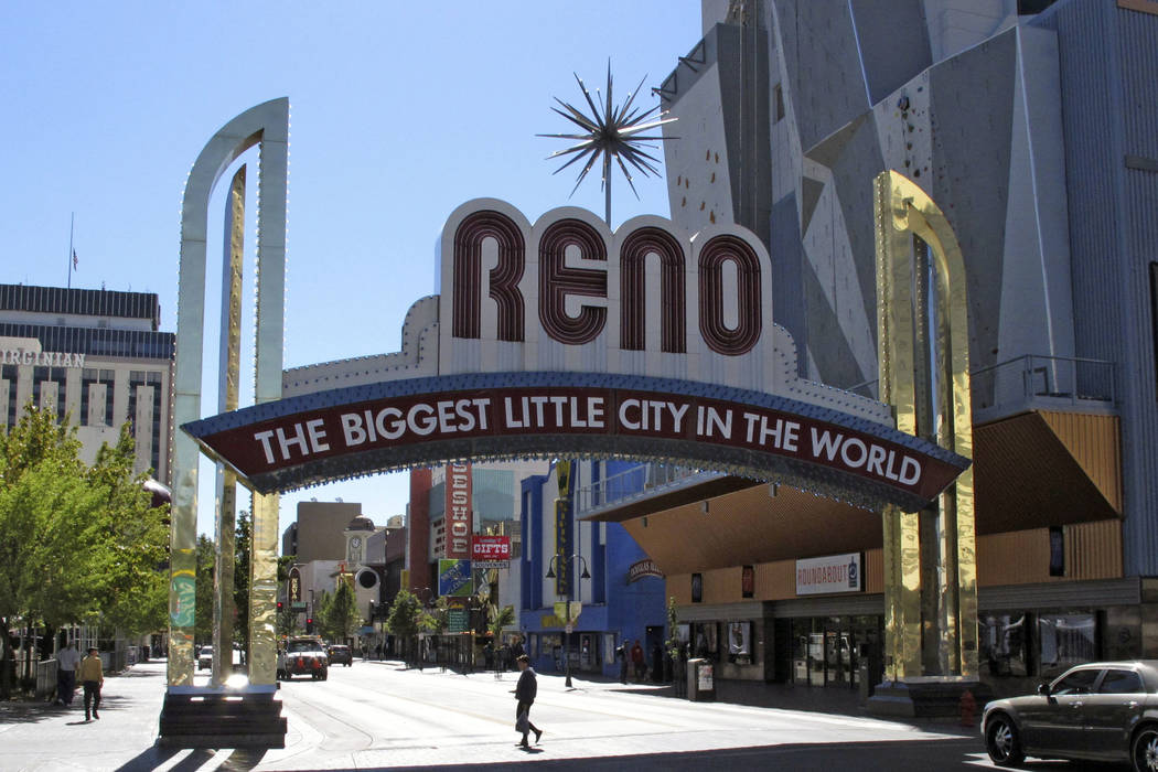 In this Oct. 11, 2016 file photo, pedestrians pass beneath the famous Reno arch as traffic passes on Virginia Street in downtown Reno, Nev. (AP Photo/Scott Sonner)