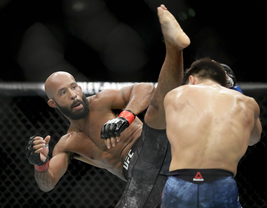 Henry Cejudo, right, ducks a kick from Demetrious Johnson during their UFC flyweight title mixed martial arts bout at UFC 227 in Los Angeles, Saturday, Aug. 4, 2018. (AP Photo/Chris Carlson)
