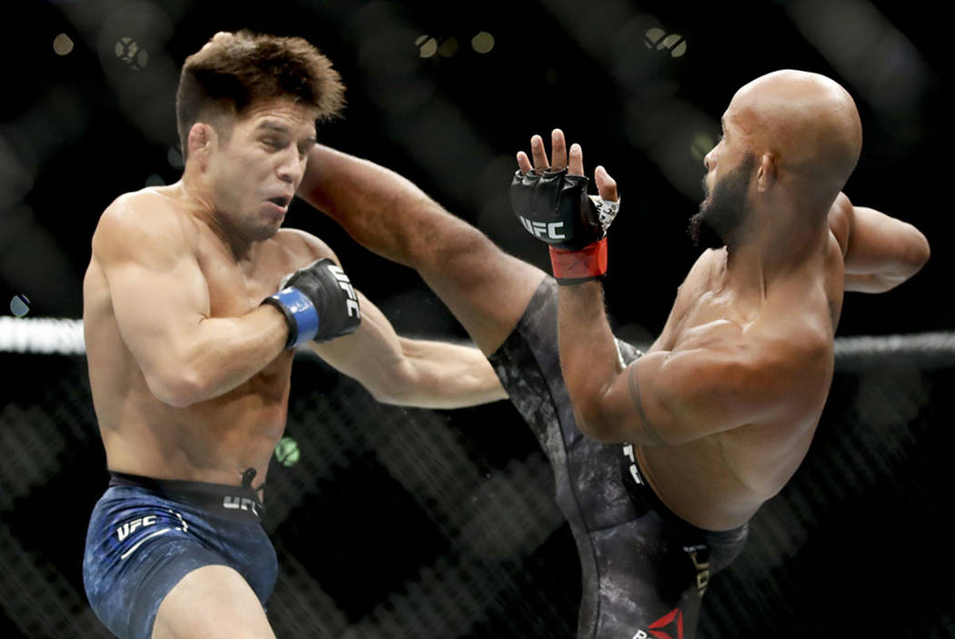 Demetrious Johnson kicks Henry Cejudo during their UFC flyweight title mixed martial arts bout at UFC 227 in Los Angeles, Saturday, Aug. 4, 2018. (AP Photo/Chris Carlson)