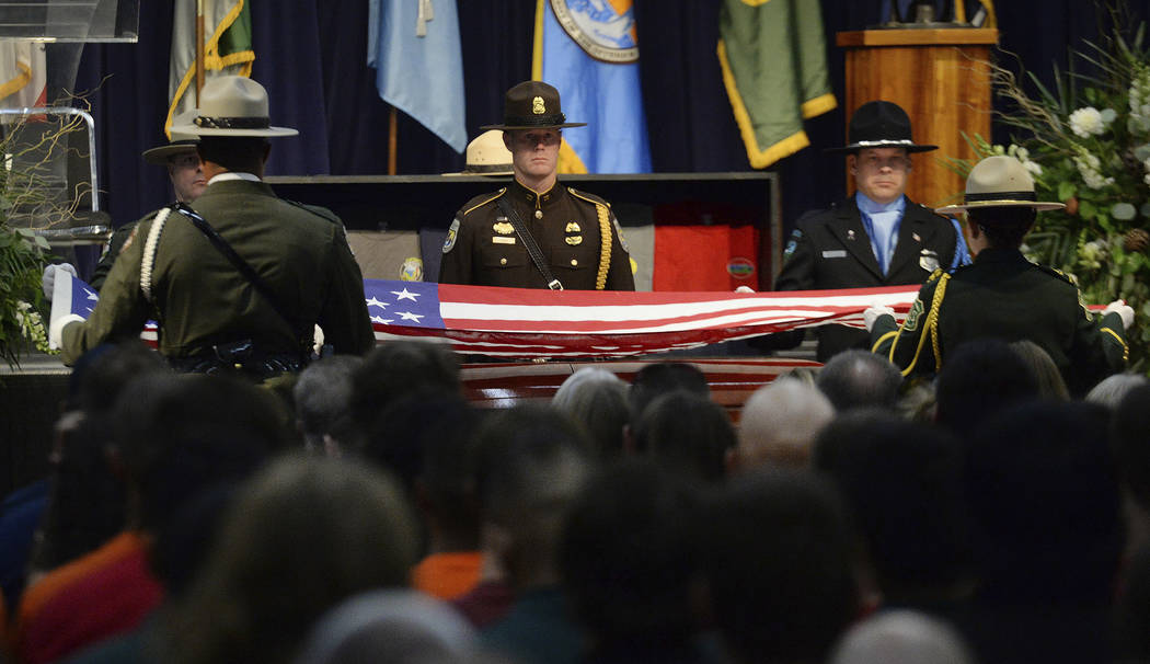 Honor guard members prepare to fold an American flag before presenting it to family members of Brian Hughes, a captain with the Arrowhead Interagency Hotshots who was killed by a falling tree whil ...