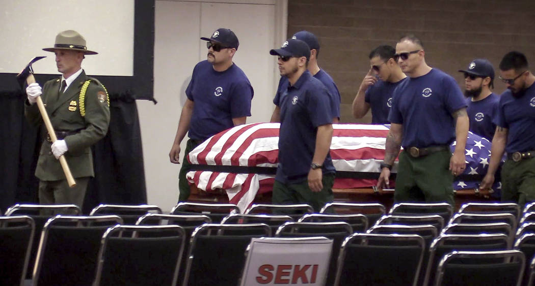 Honor guard and pall bearers carry the coffin of Brian Hughes, a captain with the Arrowhead Interagency Hotshots who was killed by a falling tree while fighting the Ferguson Fire, during a memoria ...