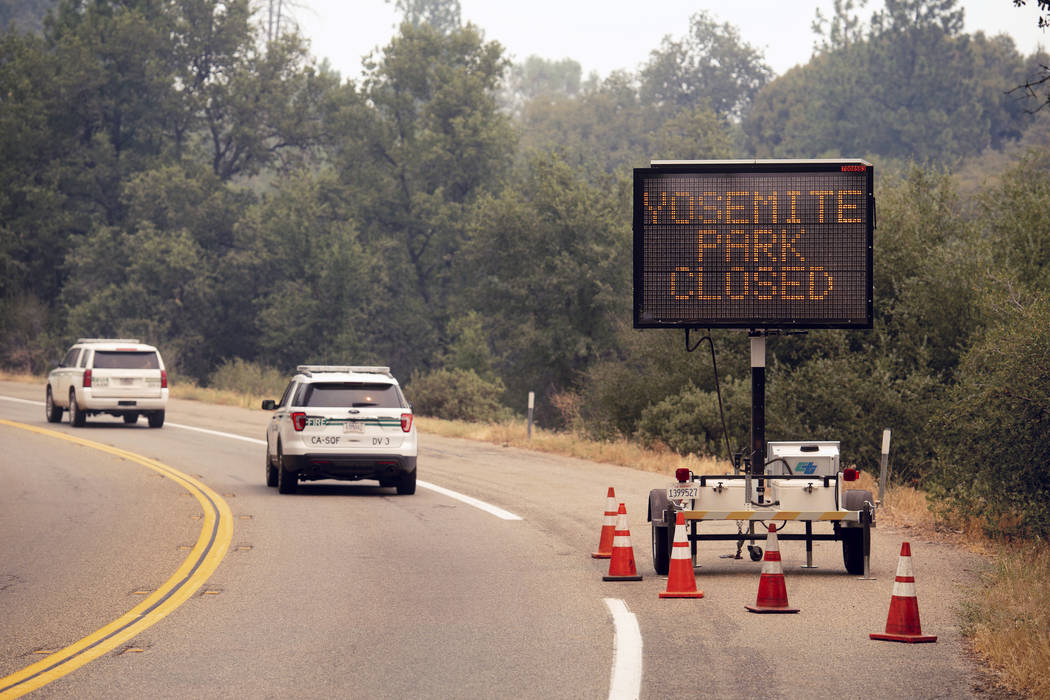 A sign on Highway 41 announces the closure of Yosemite National Park near Oakhurst, Calif.,July 25, 2018. Yosemite National Park could reopen its scenic valley and other areas Monday, Aug. 6, 2018 ...