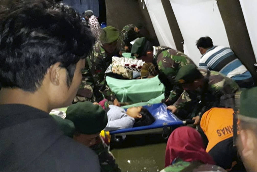 Indonesian soldiers tend to a woman injured in the earthquake at a makeshift hospital in Lombok, Indonesia, Sunday, Aug. 5, 2018. A strong earthquake struck Indonesia's popular tourist island of L ...