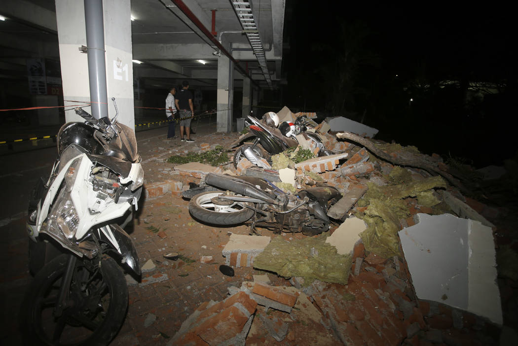Debris on top of a motorcycles after an earthquake in Bali, Indonesia, Sunday, Aug. 5, 2018. A strong earthquake struck the Indonesian tourist island of Lombok on Sunday, killing at least three pe ...