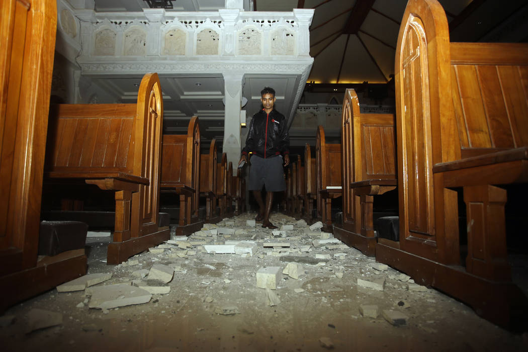 A man walks inside a cathedral where debris has fallen after an earthquake in Bali, Indonesia, Sunday, Aug. 5, 2018. A strong earthquake struck the Indonesian tourist island of Lombok on Sunday, k ...