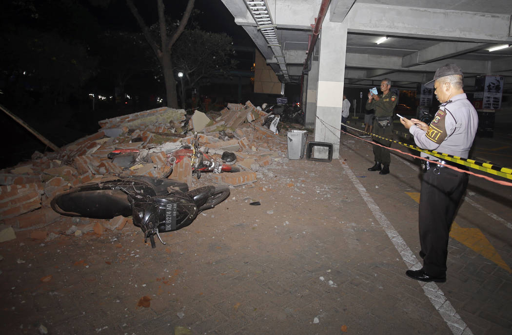 Police at the scene of debris on top of a motorcycle after an earthquake in Bali, Indonesia, Sunday, Aug. 5, 2018. A strong earthquake struck the Indonesian tourist island of Lombok on Sunday, kil ...