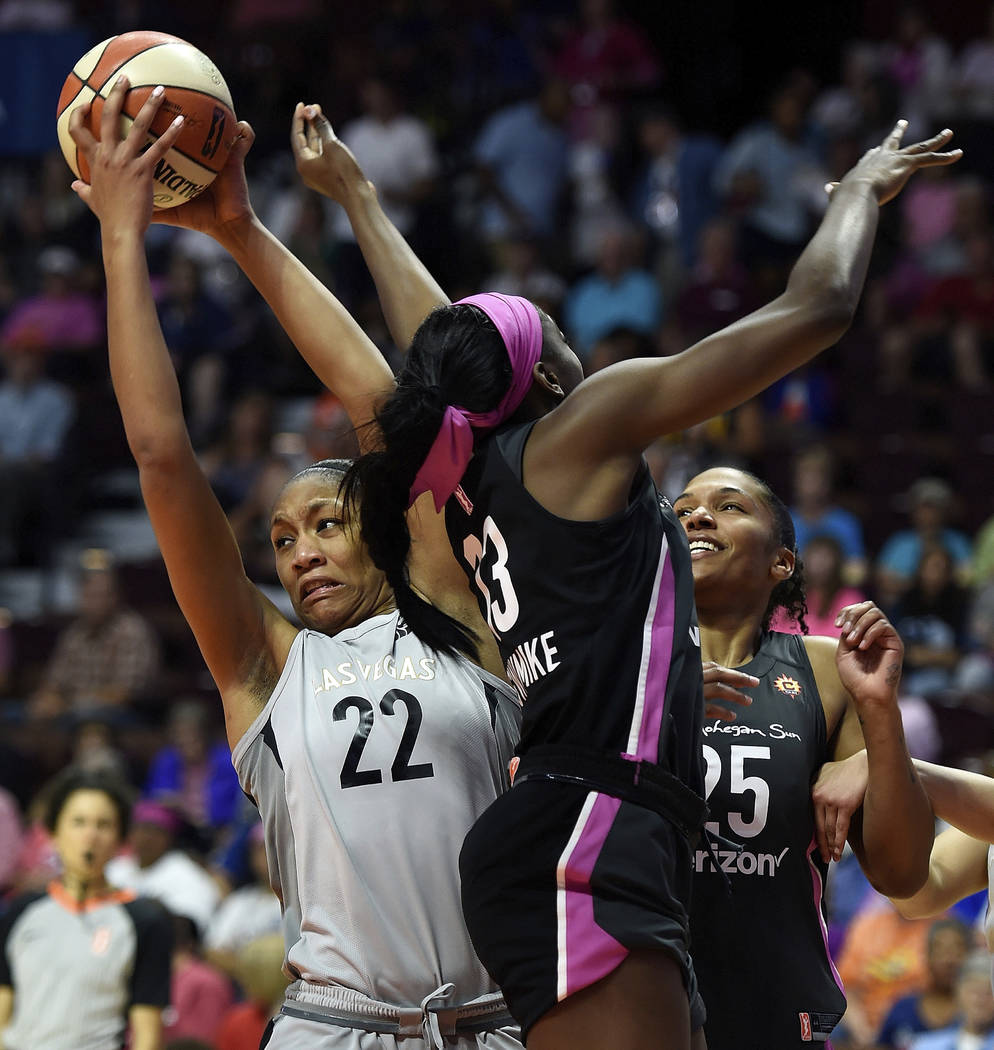 Las Vegas Aces forward A'ja Wilson (22) takes a rebound away from Connecticut Sun forward Chiney Ogwumike (13) and Alyssa Thomas (25) in the second half of WNBA basketball game action Sunday, Aug. ...