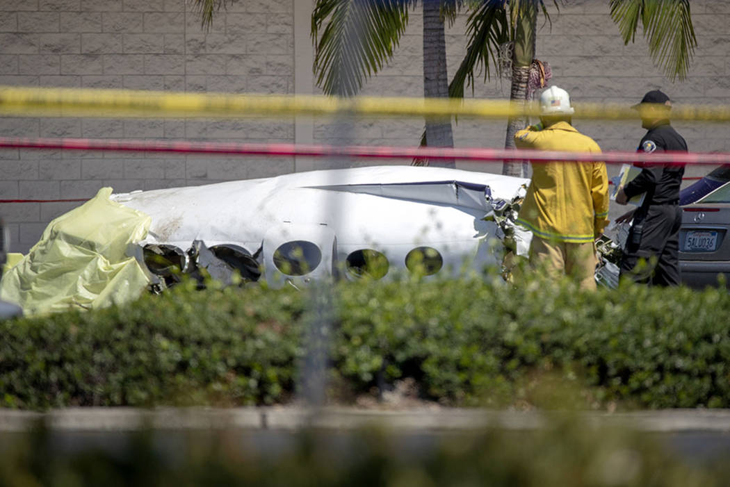 Santa Ana fire and police and Orange County Fire departments respond to the scene of a deadly plane crash in a parking lot near the intersection of Bristol and Sunflower Streets near South Coast P ...