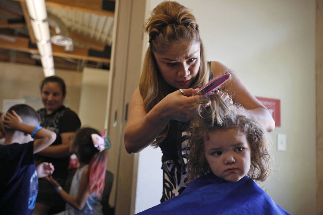 Diana Jimenz cuts the hair of Abbey Dallman, 3, at the annual Back to School Fair organized by the Happy Face Foundation at Springs Preserve in Las Vegas, Sunday, Aug. 5, 2018. Students received f ...