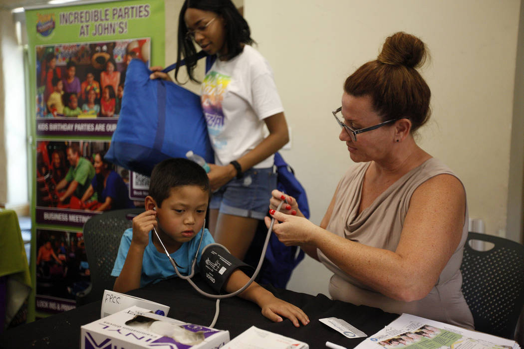 Dr. Ivonne Draughon lets Maddox Sourivong, 6, listen to his heartbeat after he received a free blood pressure reading at the annual Back to School Fair organized by the Happy Face Foundation at Sp ...