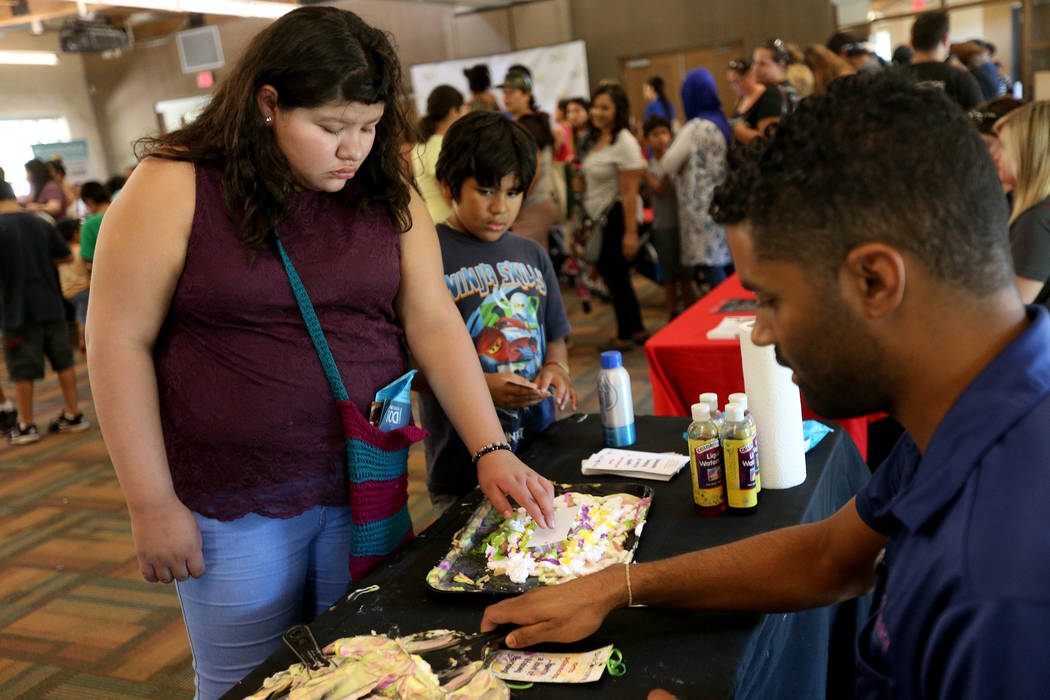 Madeline Guzman, 14, decorates a bookmark at the Children's Museum booth at the annual Back to School Fair organized by the Happy Face Foundation at Springs Preserve in Las Vegas, Sunday, Aug. 5, ...