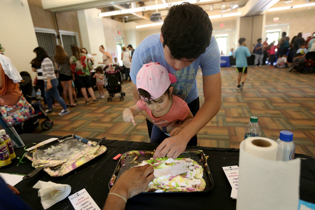 Javier Barra, 18, holds his niece Mia Taliercio, 2, as they decorate a bookmark at the Children's Museum booth at the annual Back to School Fair organized by the Happy Face Foundation at Springs P ...