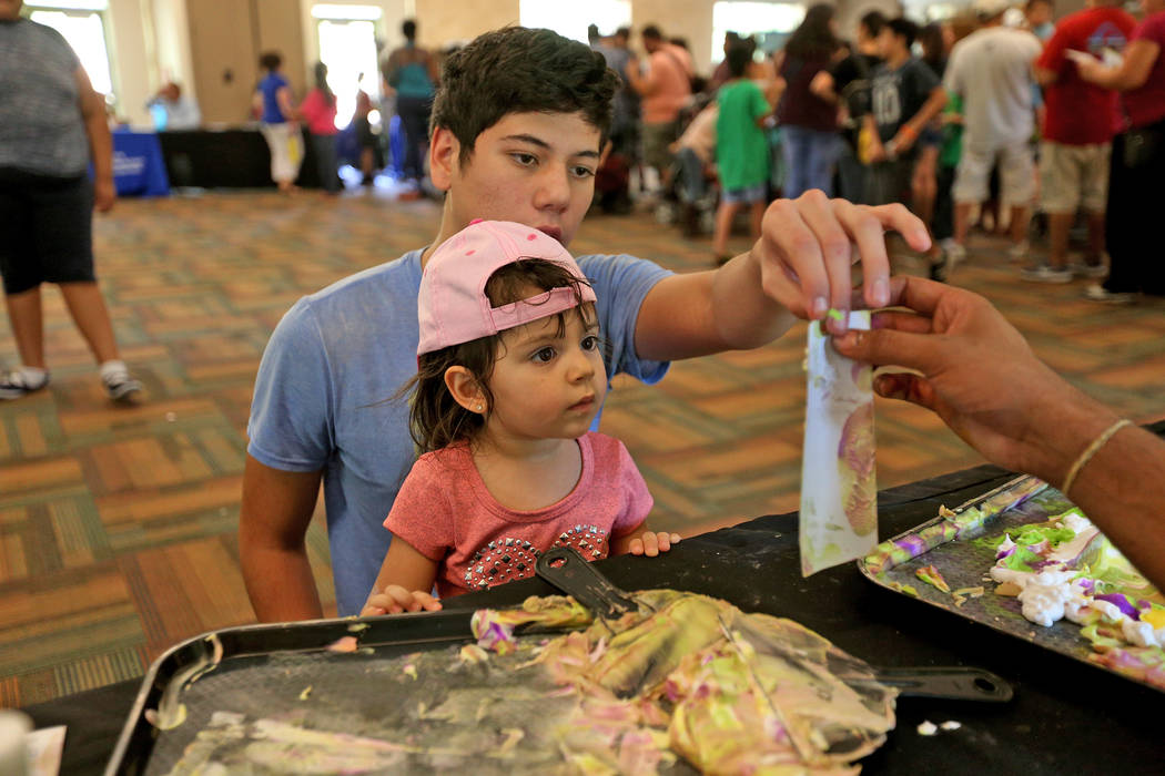 Javier Barra, 18, holds his niece Mia Taliercio, 2, complete their bookmark at the Children's Museum booth at the annual Back to School Fair organized by the Happy Face Foundation at Springs Prese ...