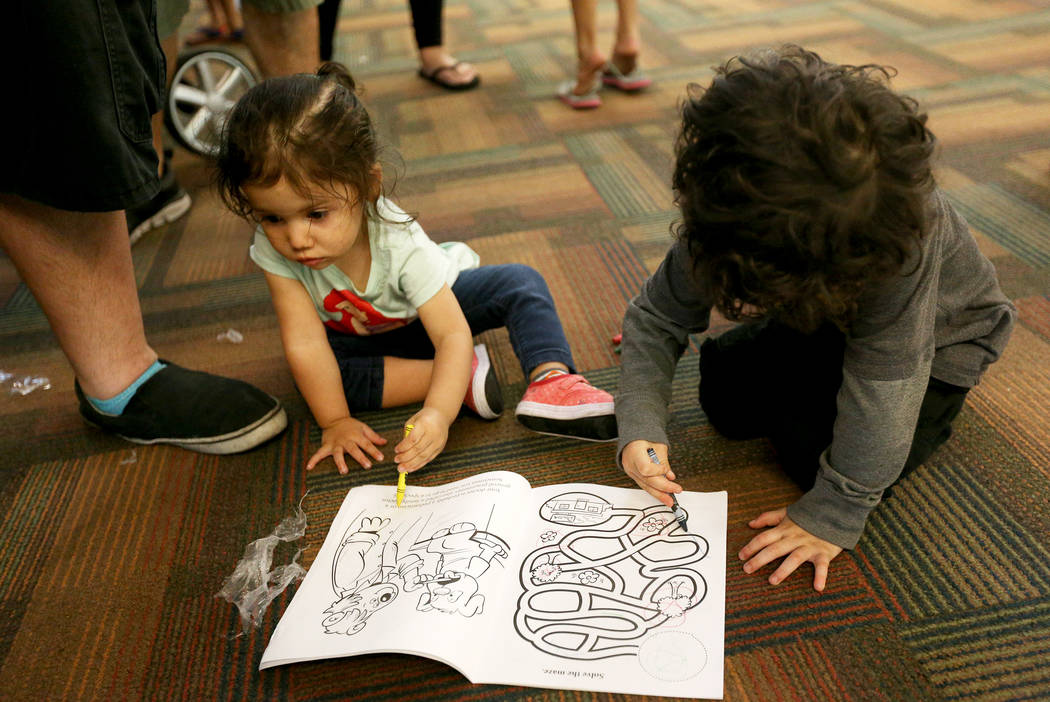 Ariel Gonzales, 1, left, and her brother Nathan Gonzales, 3, colors a coloring book they received at the annual Back to School Fair organized by the Happy Face Foundation at Springs Preserve in La ...