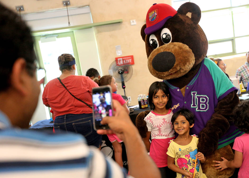 Syedrafick Syed takes a photo of his daughters Shaheen Syedrafick, 7, left, and Afreen Syedrafick, 4, with the Incredibear from John's Incredible Pizza Company at the annual Back to School Fair or ...