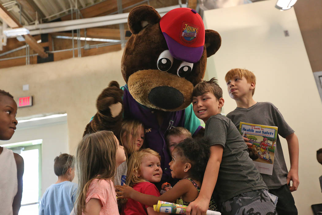 Incredibear from John's Incredible Pizza Company hugs kids at the annual Back to School Fair organized by the Happy Face Foundation at Springs Preserve in Las Vegas, Sunday, Aug. 5, 2018. Students ...