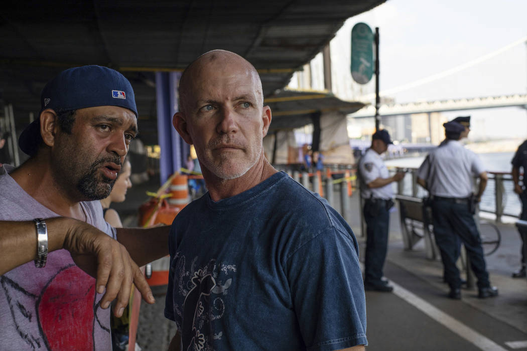 Monte Campbell, of Stillwater, Okla., right, stands under the Brooklyn Bridge in Manhattan after jumping into New York's East River to rescue a baby floating in the water, Sunday, Aug. 5, 2018. ...