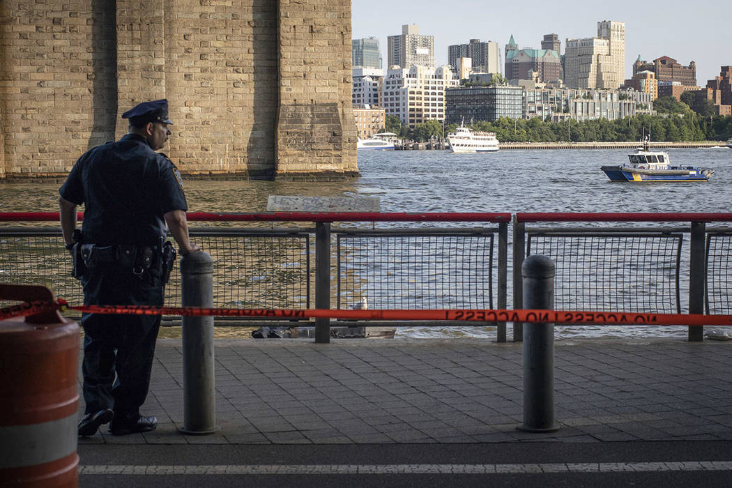A New York Police Department officer stands guard as authorities investigate the death of a baby boy who was found floating in the water near the Brooklyn Bridge in Manhattan, on Sunday, Aug. 5, 2 ...