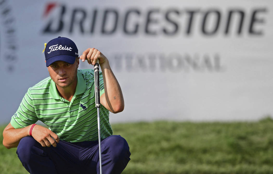 Justin Thomas reads the green on the 18th hole during the final round of the Bridgestone Invitational golf tournament at Firestone Country Club, Sunday, Aug. 5, 2018, in Akron, Ohio. (AP Photo/Dav ...
