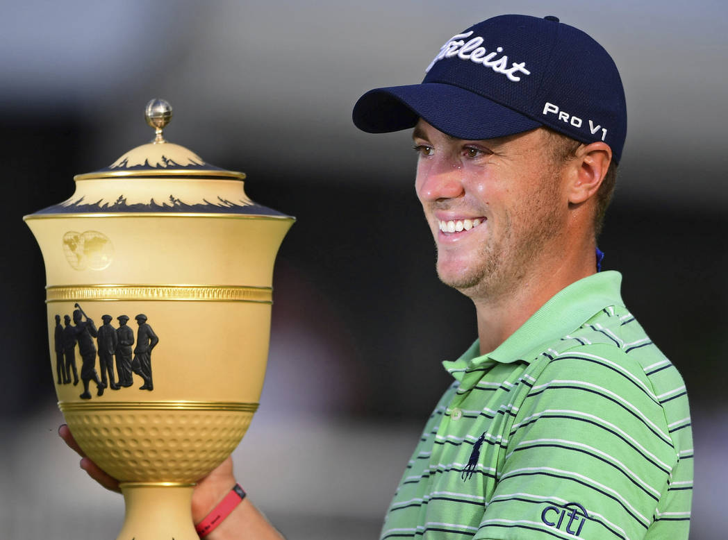 Justin Thomas holds the Gary Player Cup trophy after winning the final round of the Bridgestone Invitational golf tournament at Firestone Country Club, Sunday, Aug. 5, 2018, in Akron, Ohio. (AP Ph ...