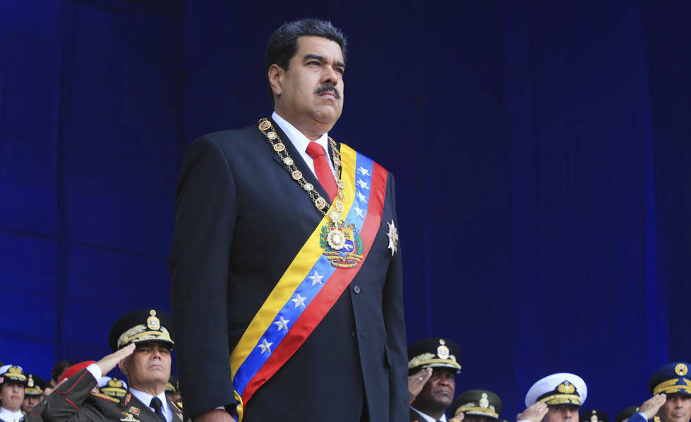 In this photo provided by the Miraflores Presidential Palace, President Nicolas Maduro stands at attention during a event marking the 81st anniversary of the National Guard, in Caracas, Venezuela, ...