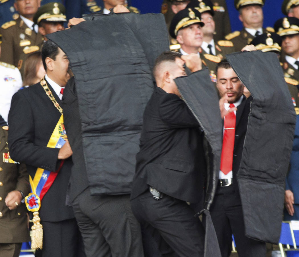 In this photo released by China's Xinhua News Agency, security personnel surround Venezuela's President Nicolas Maduro, at left, during an incident as he was giving a speech in Caracas, Venezuela, ...