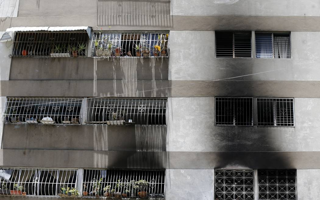 Signs of smoke cover the apartment complex where an allegedly armed drone crashed, causing a fire, in Caracas, Venezuela, Sunday, Aug. 5, 2018. Venezuelan President Nicolas Maduro dodged an appare ...