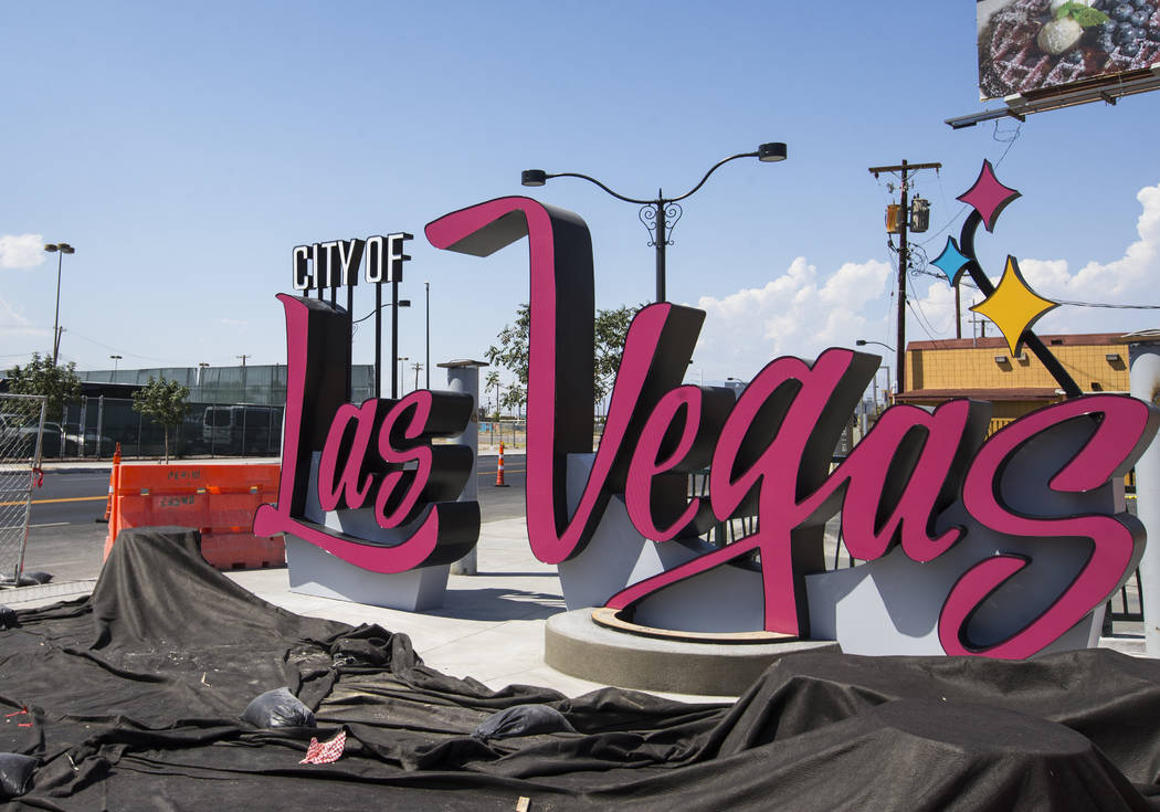 A sign bearing the City of Las Vegas logo that originally debuted in 2016 is shown under construction at the intersection where Las Vegas Boulevard splits off to Main Street in downtown Las Vegas ...