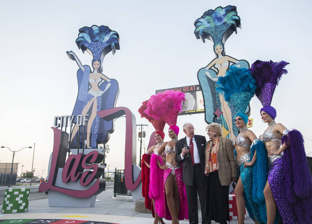 Las Vegas Mayor Carolyn Goodman, third from right, takes photos with her husband and former Las Vegas Mayor Oscar Goodman and a group of showgirls during a dedication ceremony for the new city of ...