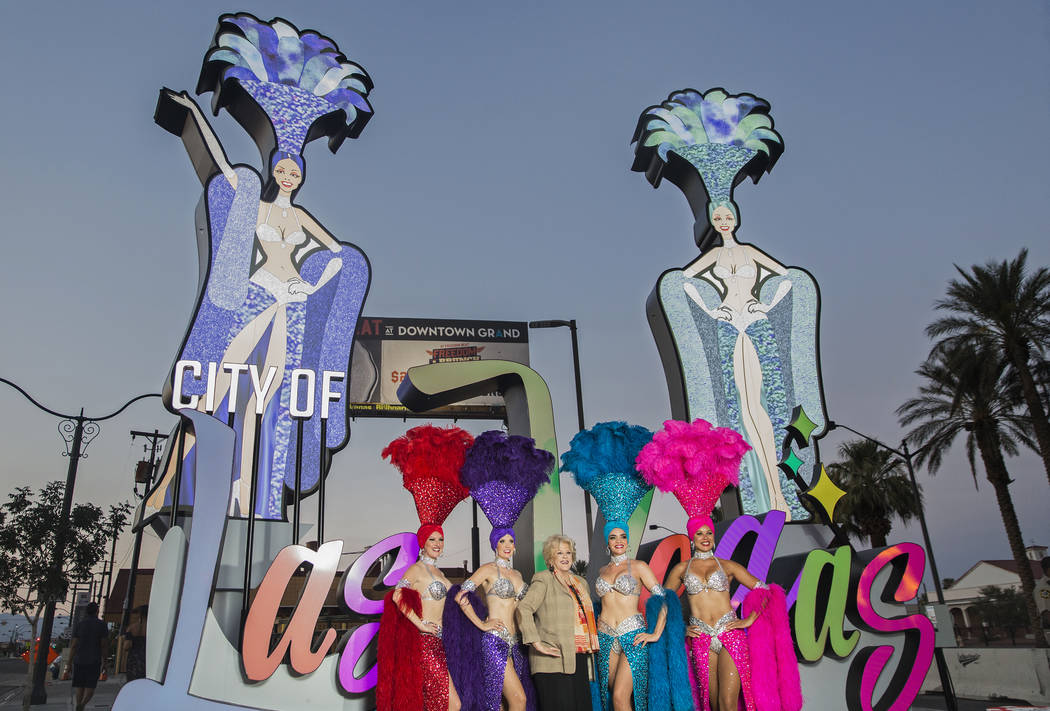 Las Vegas Mayor Carolyn Goodman, third from left, takes photos with a group of showgirls during a dedication ceremony for the new city of Las Vegas sign greeting visitors heading north on Las Vega ...