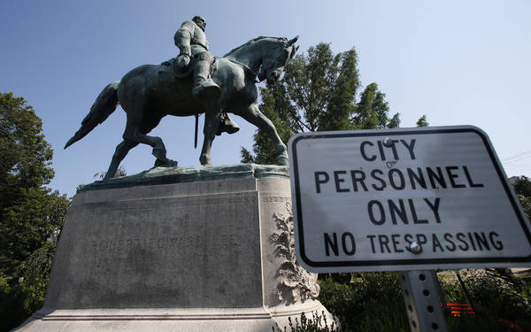 A No Trespassing sign is displayed in front of a statue of Robert E. Lee in Charlottesville, Virginia, at the park that was the focus of the Unite the Right rally, Monday, Aug. 6, 2018. Pressure t ...