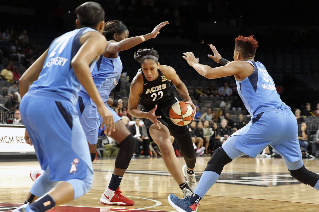 Las Vegas Aces center A'ja Wilson (22) surrounded by Atlanta Dream's Renee Montgomery, left, and Renee Montgomery, right, in the first half of a WNBA basketball game at the Mandalay Bay Event Cent ...