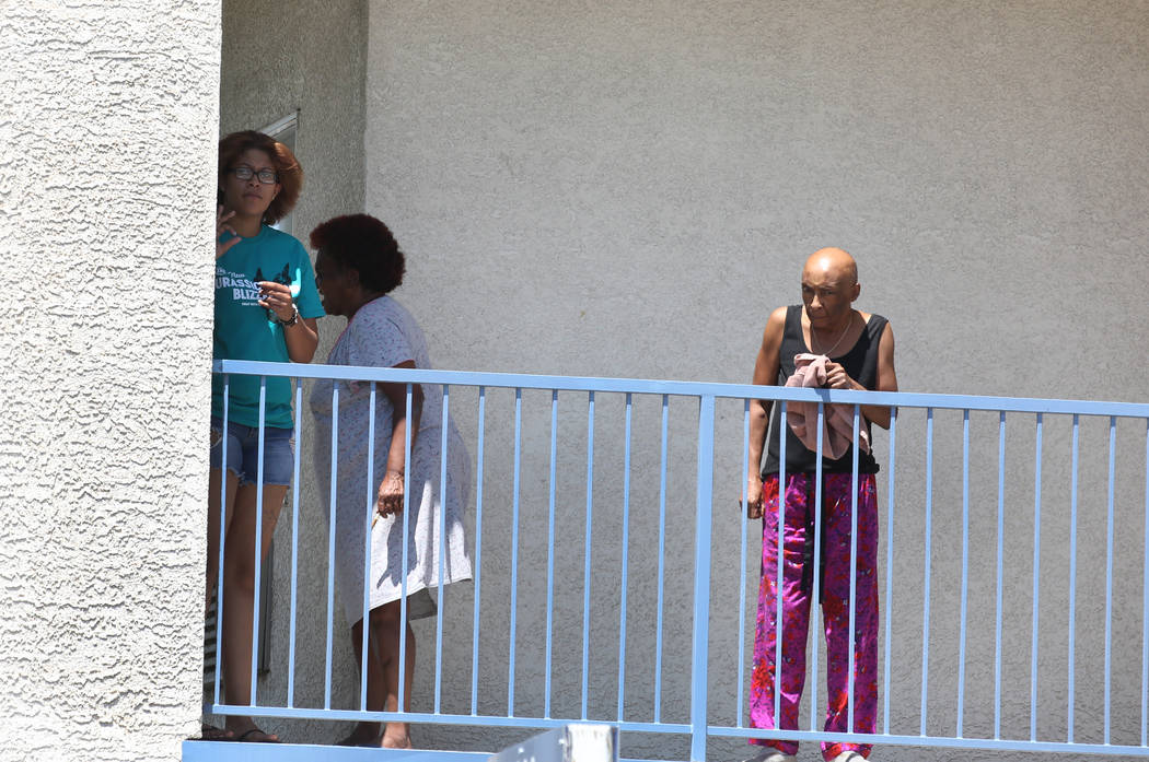 Residents at Kensington Suites in the 2200 block of West Bonanza Road watch as Las Vegas police are investigating at the scene of an officer-involved shooting, Monday, Aug. 6, 2018. It's the third ...